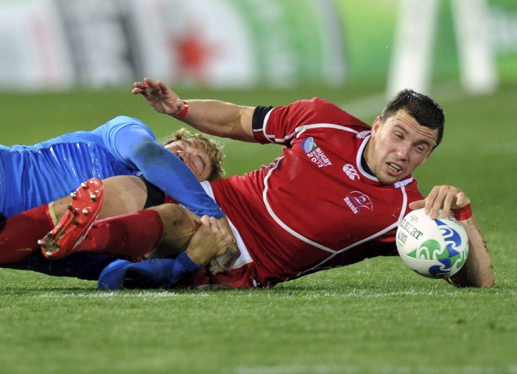FILE - In this Tuesday Sept. 20, 2011 file photo, Russia's Vasily Artemyev frees the ball in the tackle by Italy's Giulio Toniolatti, left, during the