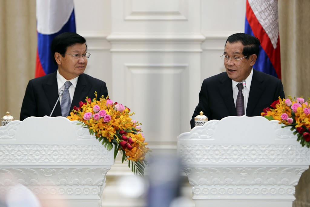 Cambodian Prime Minister Hun Sen, right, talks with his Laos counterpart Thonloun Sisoulith during a press conference, in Phnom Penh, Cambodia, Thursd...