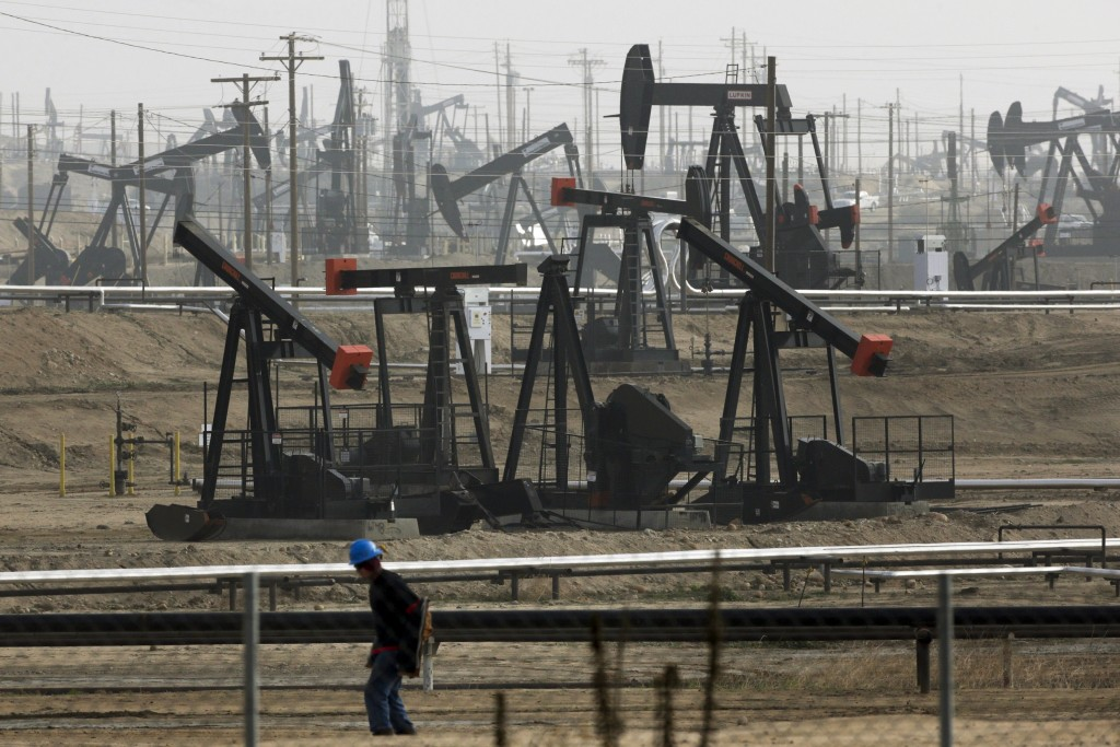 FILE - This Jan. 16, 2015, file photo shows pumpjacks operating at the Kern River Oil Field, in Bakersfield, Calif. Some Democratic presidential hopef...
