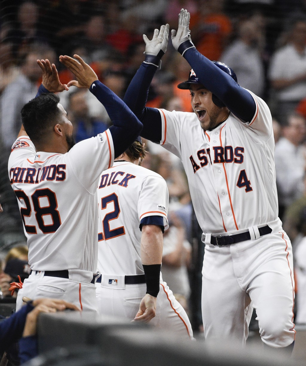 Houston Astros' George Springer (4) celebrates his solo home run off Oakland Athletics starting pitcher Brett Anderson with Robinson Chirinos during t...