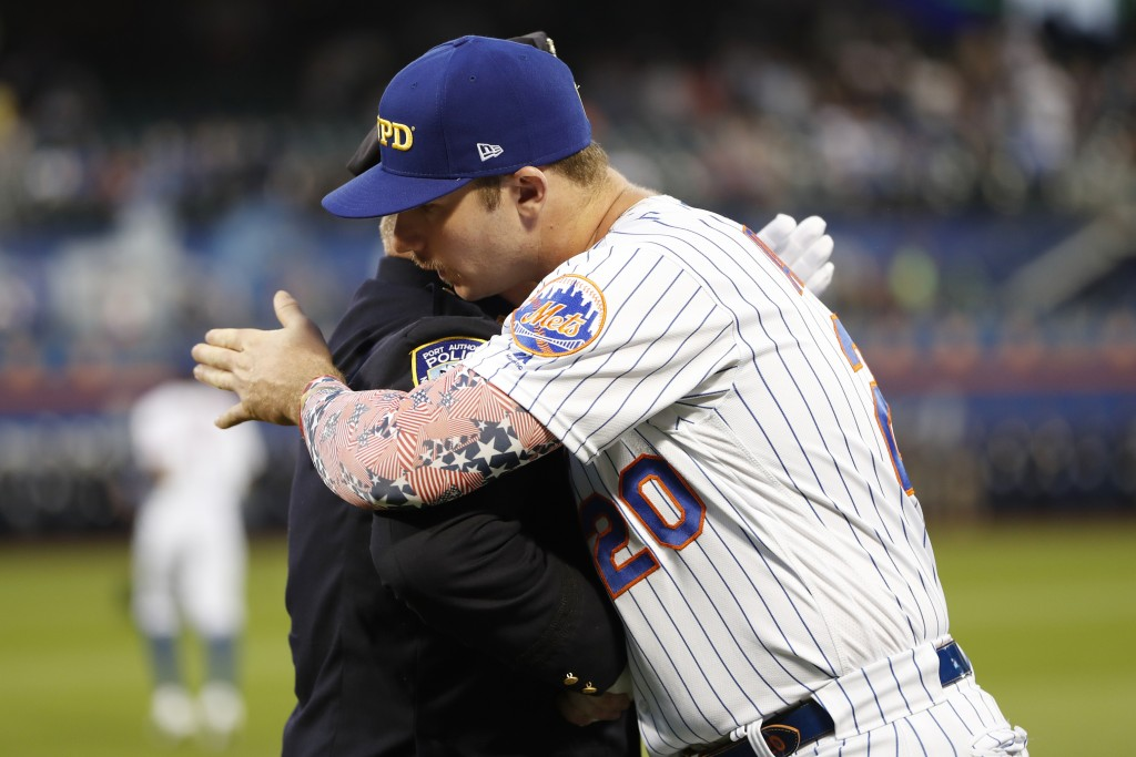 New York Mets' Pete Alonso embraces a member of the New York City Fire Department following a Sept. 11, 2001, tribute on the field before a baseball g