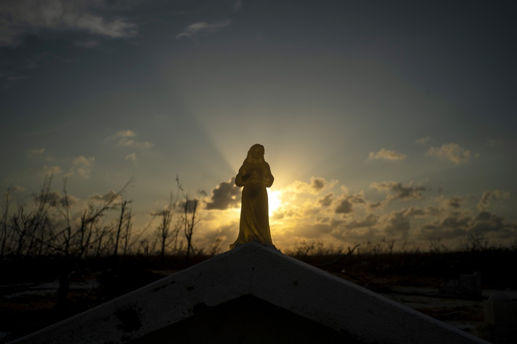 The sun sets behind a statuette of the Virgin Mary atop a grave broken by the force of Hurricane Dorian, in the cemetery of Mclean's Town, Grand Baham