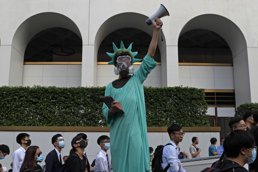 A protester dressed as the Statue of Liberty poses as people march past from Charter Garden to the U.S. Consulate in Hong Kong, Sunday, Sept. 8, 2019.