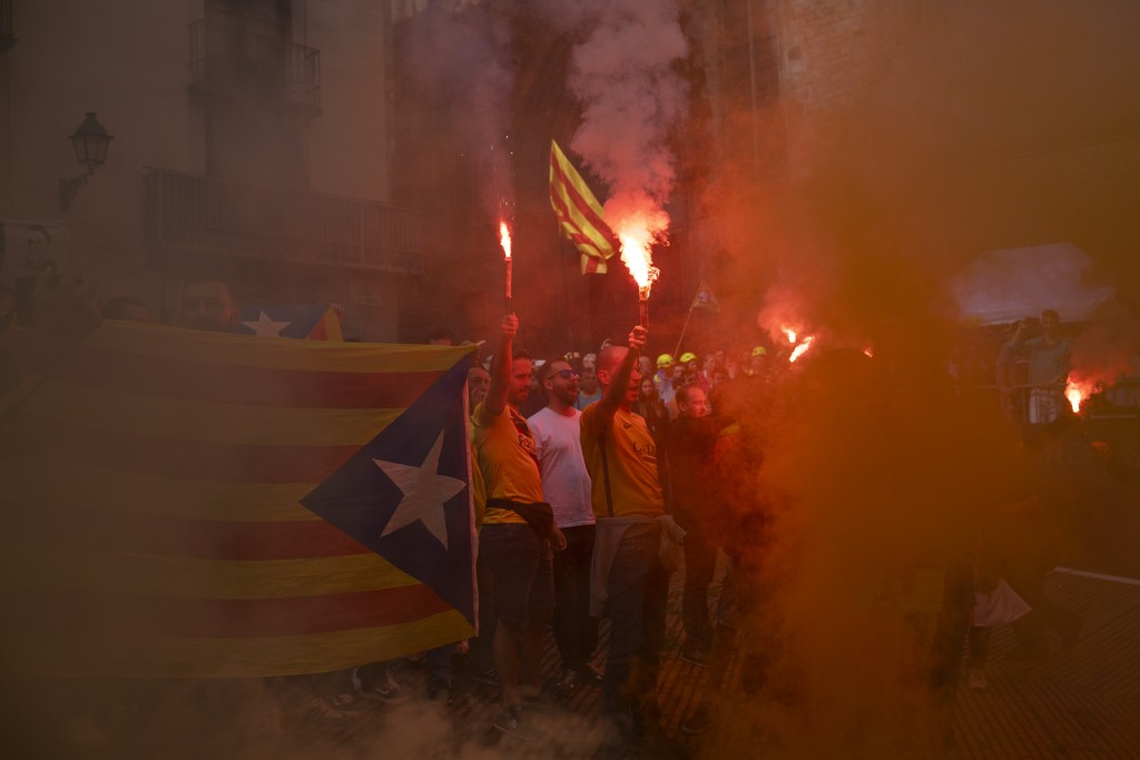 Protesters hold independence flags and flares during the Catalan National Day in Barcelona, Spain, Wednesday, Sept. 11, 2019. The traditional Septembe