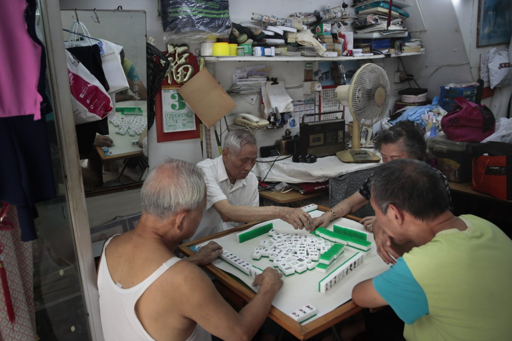 In this Sept. 3, 2019, a group of elderly people play mahjong at a shop in Hong Kong. Life is not quite normal after three months of steady protests i...