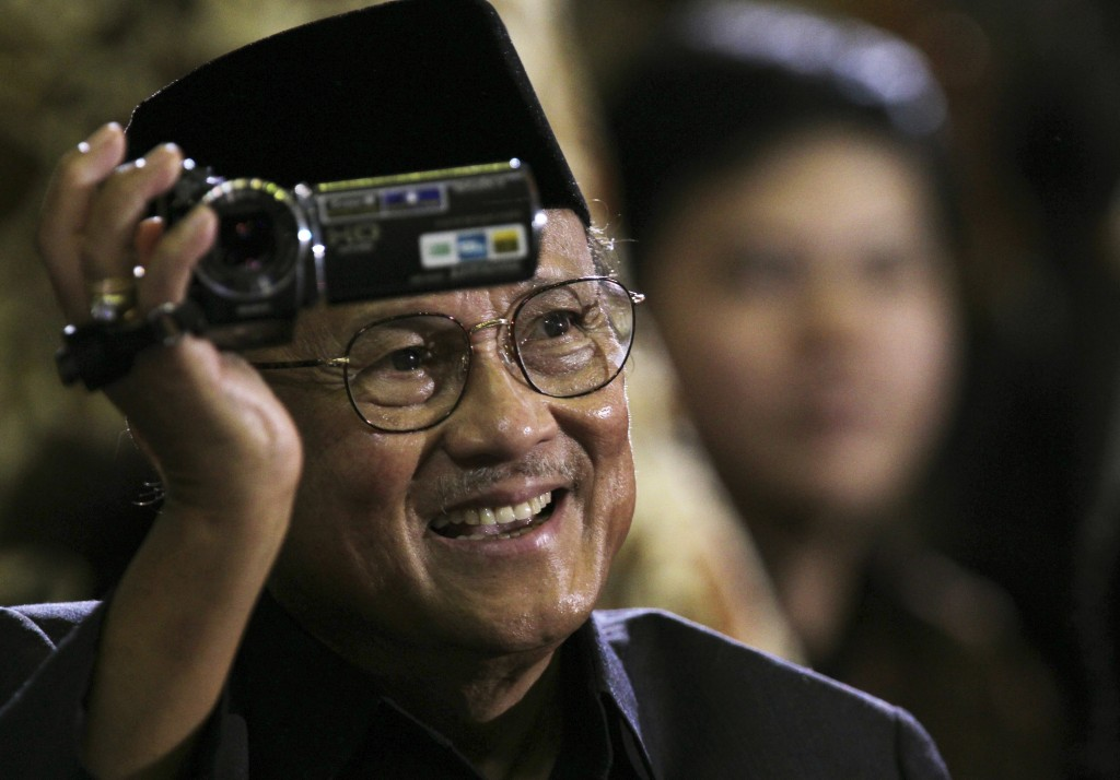 FILE - In this Nov. 10, 2010, file pool photo, former Indonesian President B.J. Habibie films the crowd as he sits in the audience to hear U.S. Presid...