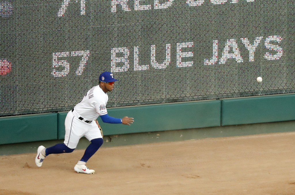 Texas Rangers right fielder Willie Calhoun chases down a double by Tampa Bay Rays' Tommy Pham in the first inning of a baseball game in Arlington, Tex...