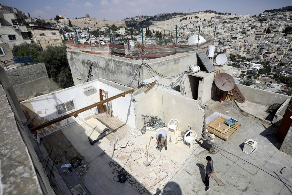 In this Monday, Sept. 9, 2019 photo, Palestinian Jamil Masalmeh uses a power tool to destroy an apartment he had added to his home years earlier, in t...