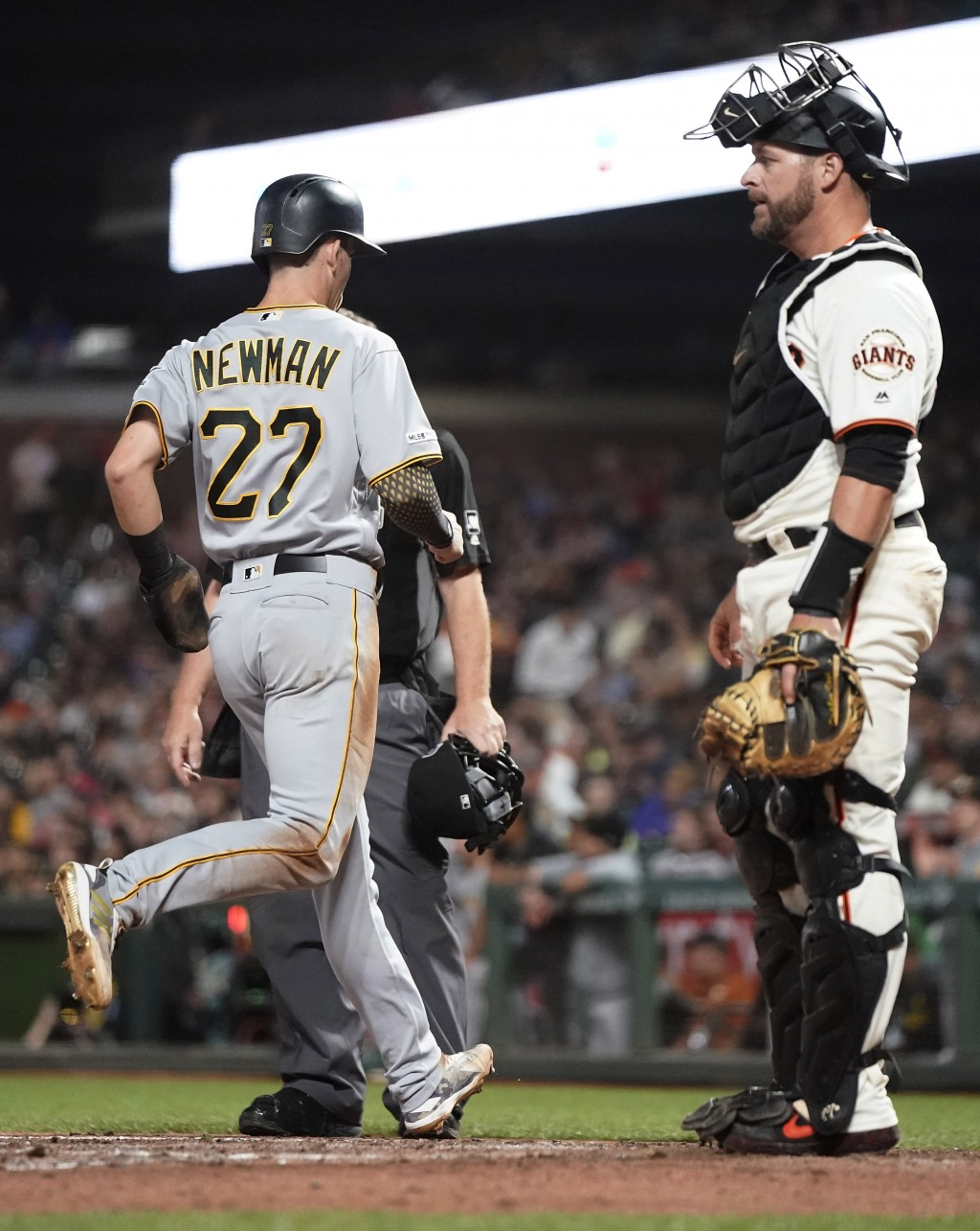 Pittsburgh Pirates' Kevin Newman (27) scores a run past San Francisco Giants catcher Stephen Vogt, right, on a single by Colin Moran during the fifth
