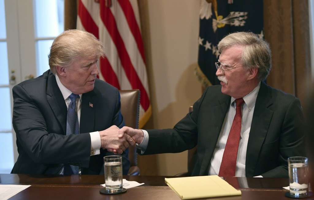 FILE - In this April 9, 2018 file photo, President Donald Trump, left, shakes hands with national security adviser John Bolton in the Cabinet Room of