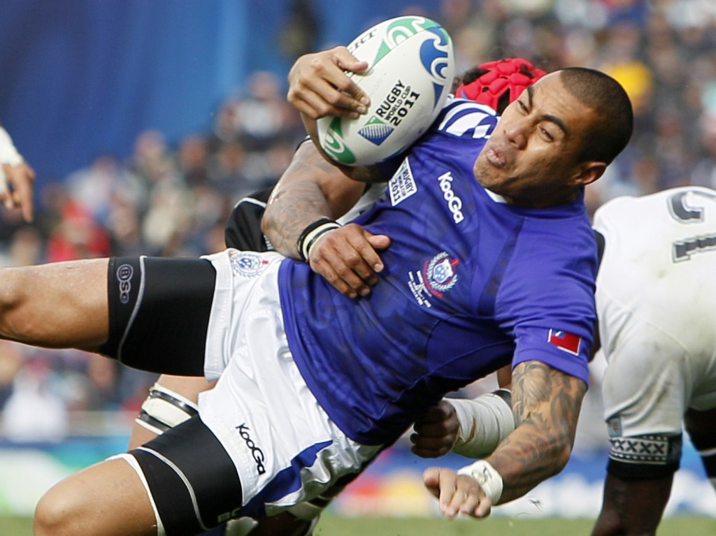 FILE - In this Sunday, Sept. 25, 2011 file photo, Samoa's Tusi Pisi is tackled by Fiji's Netani Talei during their Rugby World Cup game in Auckland, N