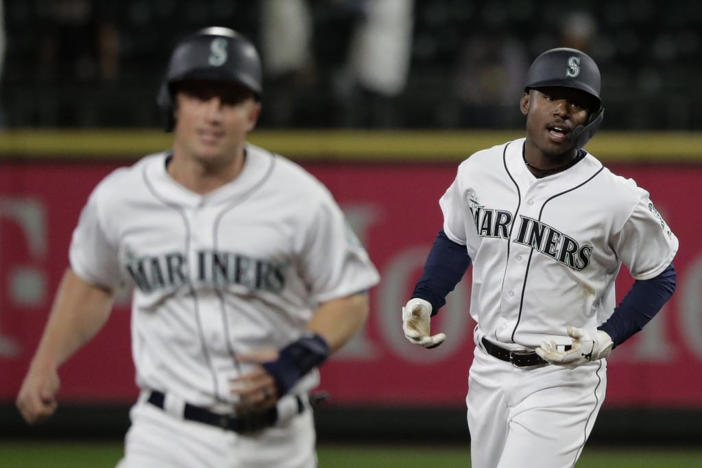 Seattle Mariners' Kyle Lewis, right, rounds the bases with Kyle Seager, left, after Lewis hit a three-run home run against the Cincinnati Reds during ...
