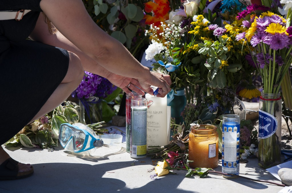 A woman relights a candle placed at a memorial for the victims of the Conception dive boat on the Santa Barbara Harbor on Sunday, Sept. 8, 2019 in San