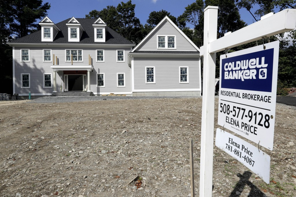In this Sept. 3, 2019, photo a sign rests in front of a newly constructed home, in Westwood, Mass. On Thursday, Sept. 12, Freddie Mac reports on this