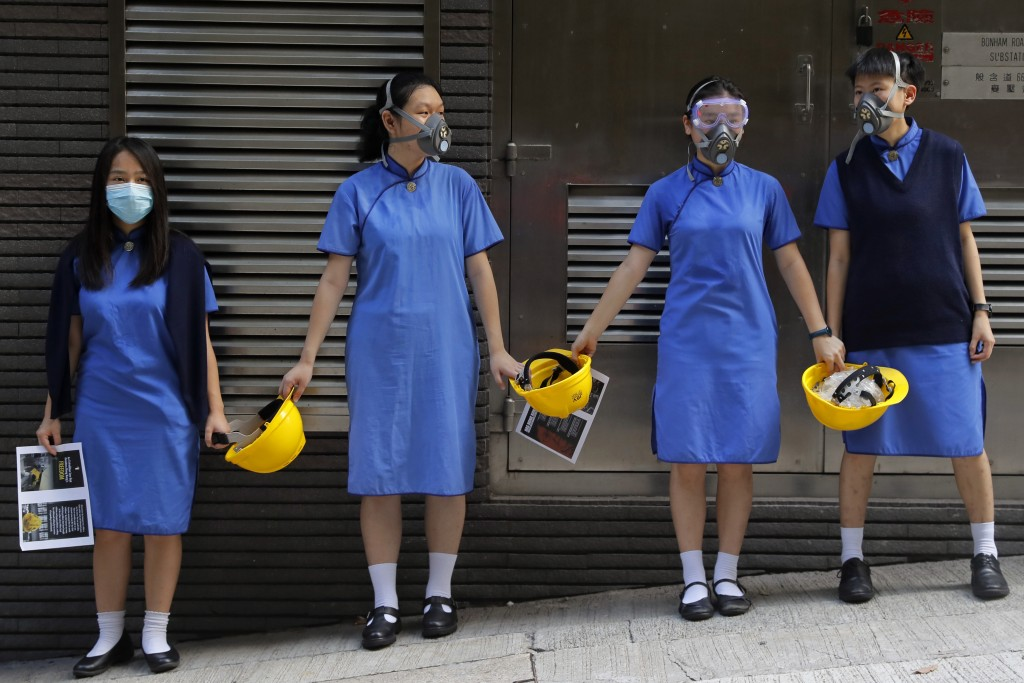 Students wearing mask hold hands to surround the St. Stephen's Girls' College in Hong Kong, Monday, Sept. 9, 2019. Thousands of demonstrators in Hong