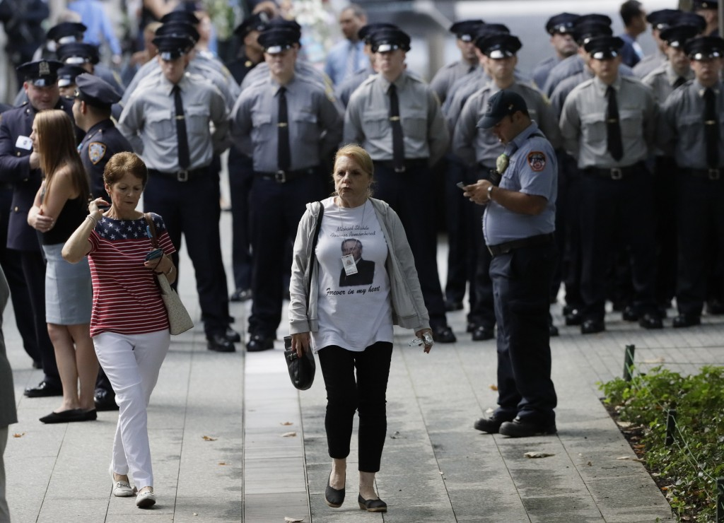 People gather for a ceremony marking the 18th anniversary of the attacks of Sept. 11, 2001 at the National September 11 Memorial, Wednesday, Sept. 11,...