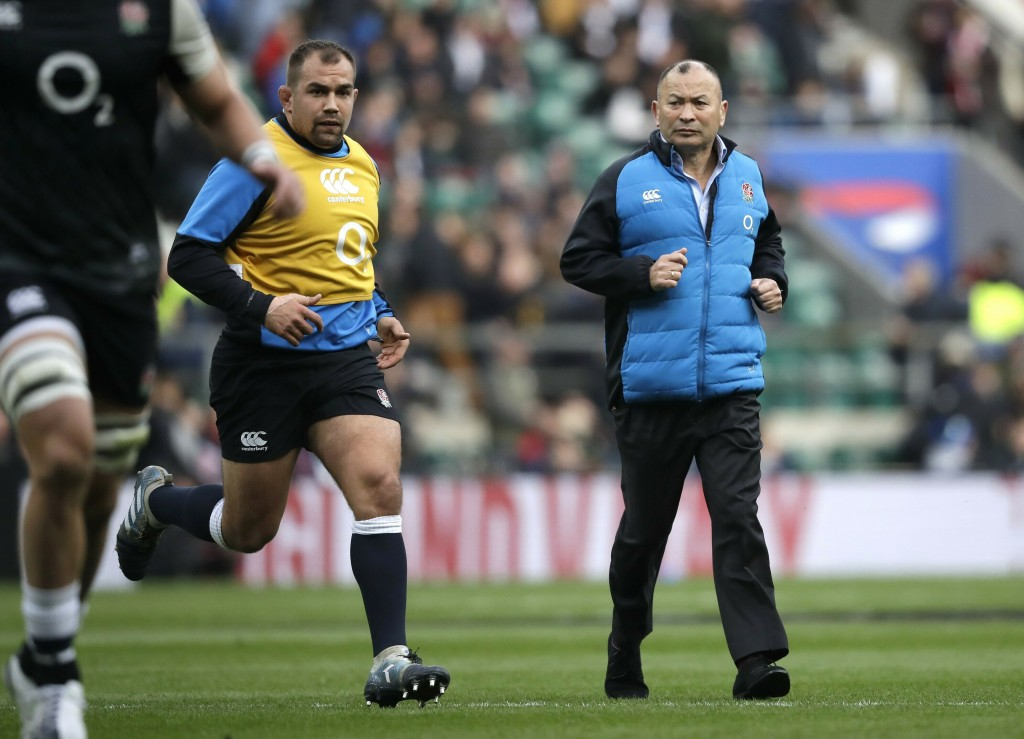 FILE - In this Saturday, March 9, 2019, file photo, England head coach Eddie Jones, right, watches his players warm up ahead of their Six Nations rugb