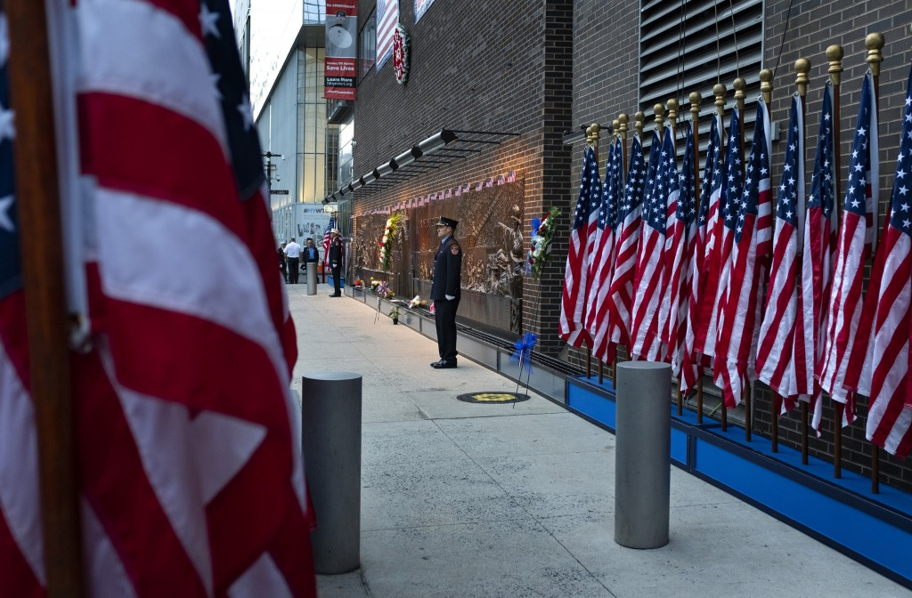 New York City firefighters stand at attention in front of a memorial on the side of a firehouse adjacent to One World Trade Center and the 9/11 Memori