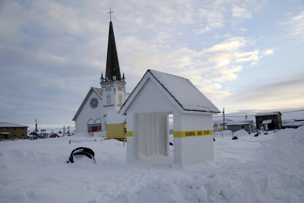 In this Feb. 14, 2019, photo, a school bus stop stands in front of Old St. Joe's Hall, built in 1901 by a Jesuit priest in Nome, Alaska. (AP Photo/Won...