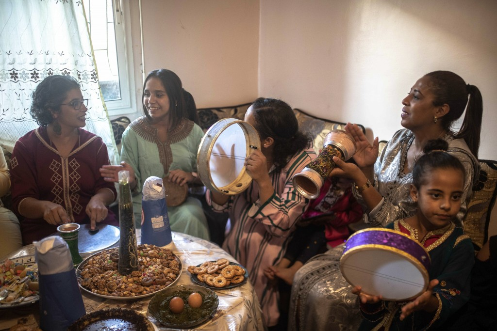 In this Tuesday, Sept. 10, 2019 photo, women and children gather at a home to celebrate the occasion of Ashura, in Sale, near Rabat, Morocco. On Sept....