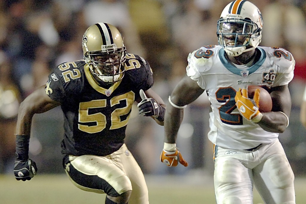 FILE - In this Sunday, Oct. 30, 2005 file photo, running back Ronnie Brown (23) runs against New Orleans Saints linebacker Sedrick Hodge (52) gives ch