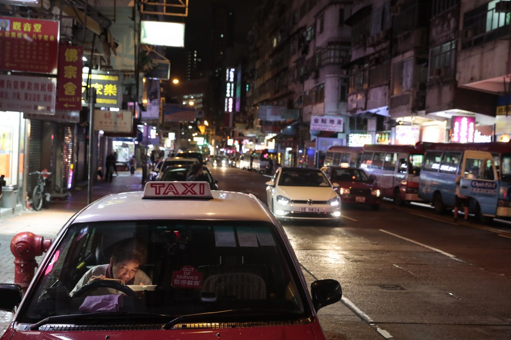 In this Sept. 2, 2019, photo, a taxi driver eats his late dinner in his car near the Temple Street Night Market in Hong Kong. Life is not quite normal...