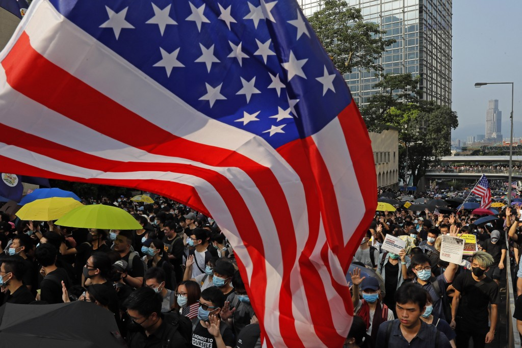"""Protesters wave U.S. flags in Hong Kong, Sunday, Sept. 8, 2019. Thousands of demonstrators in Hong Kong urge President Donald Trump to """"liberate"""" the"""