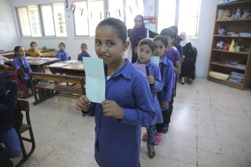 FILE - In this July 20, 2017 file photo, Syrian refugee children between the ages of six and 12 line up in a first-grade classroom for a lesson in sum