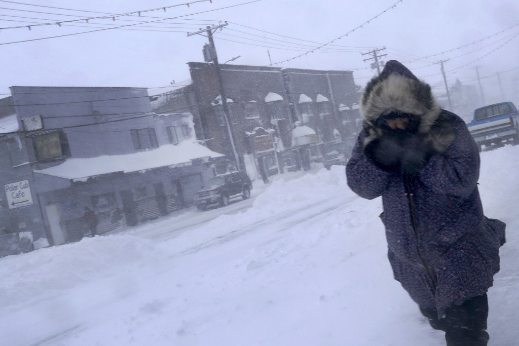 In this Feb. 23, 2019, photo, a woman shields her face from the wind during a snow storm as she walks on Front Street in Nome, Alaska. (AP Photo/Wong ...