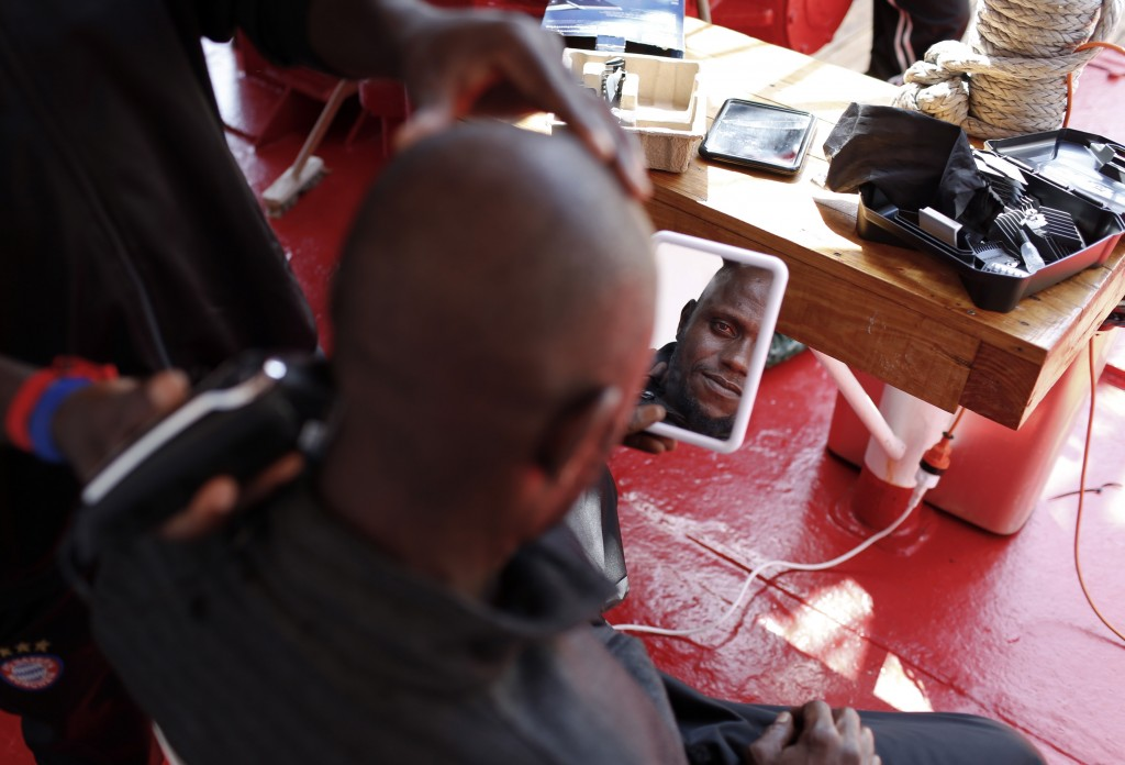 Mouctar Diallo, from Guinea, looks at himself in the mirror as he gets his hair shaved aboard the Ocean Viking humanitarian rescue ship, in the Medite...
