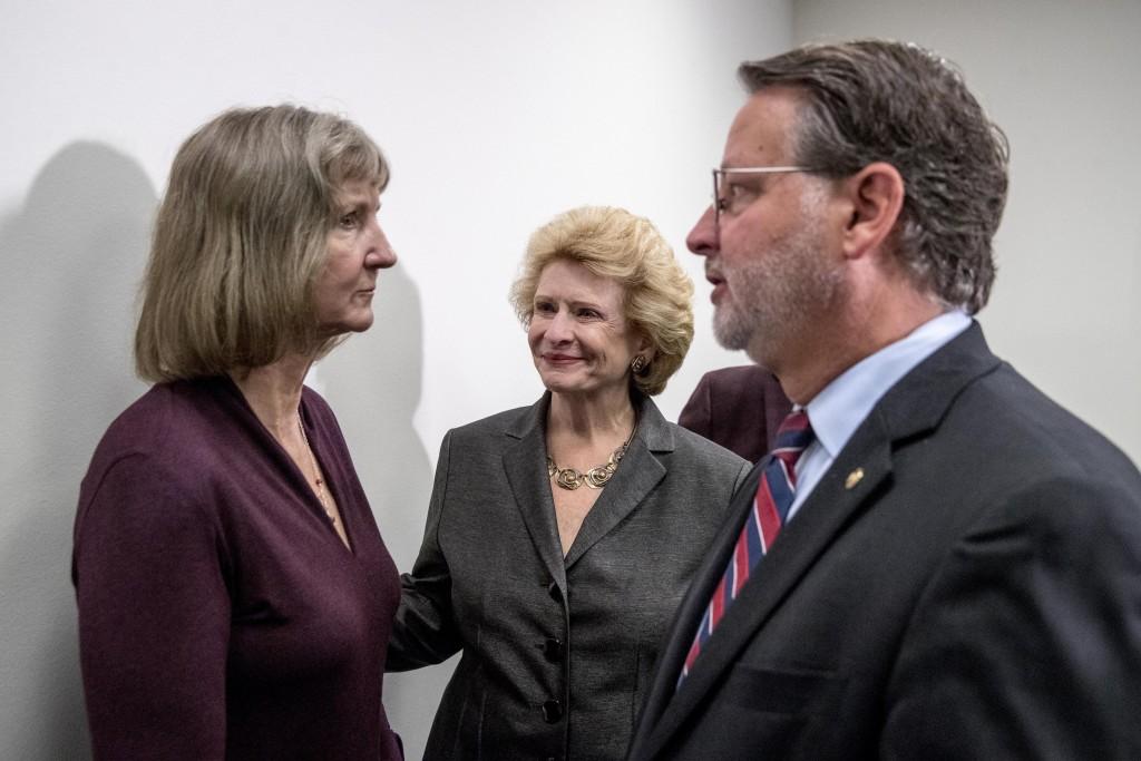 Sen. Gary Peters., right, Sen. Debbie Stabenow, D-Mich., center, and Elizabeth Whelan, the sister of Paul Whelan, left, speak following a news confere