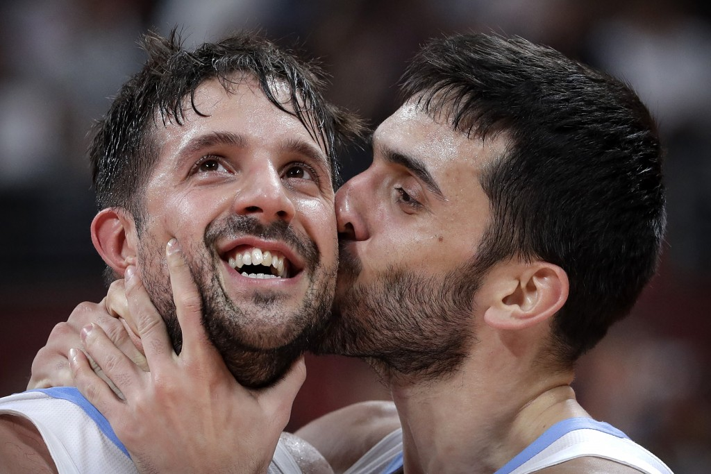 Facundo Campazzo of Argentina, right, kisses teammate Nicolas Laprovittola as they celebrate after beating France in their semifinal match against in ...