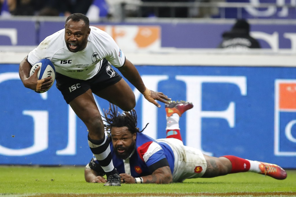 FILE - In this Nov. 24, 2018, file photo, Fiji's Vereniki Goneva evades the tackle of France's Mathieu Bastareaud as he scores a try that was disallow