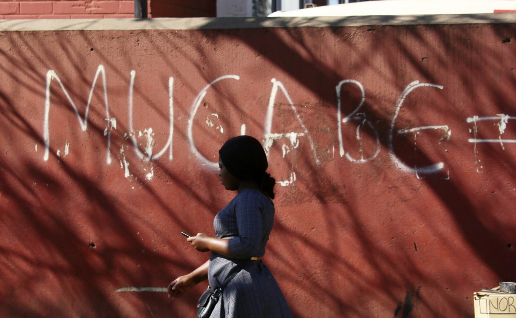 A woman walks past a graffiti sign in Harare, Sept. 6, 2019. As controversy continues around the burial of Mugabe, the capital, Harare, bustles with p