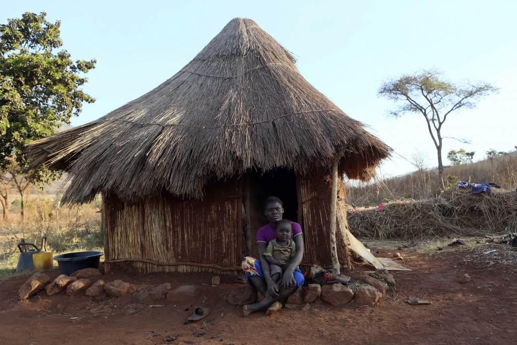 Mary Chipiro, a farm worker at Former Zimbabwean President Robert Mugabe's Dairy farm, sits with her child outside her thatched hut at the farm compou
