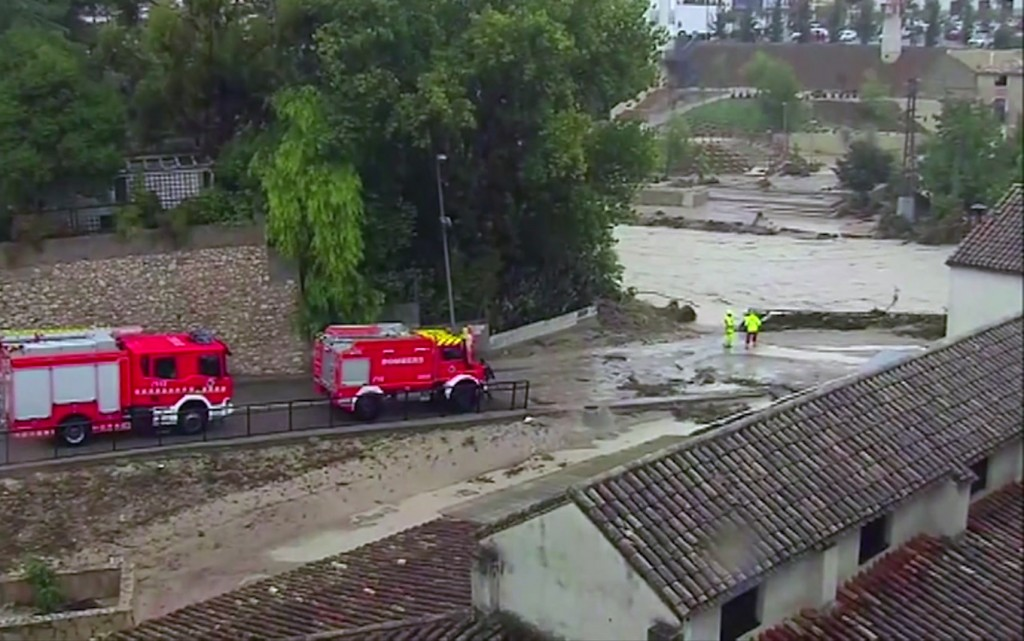 In this image made from video provided by Atlas, fire engines drive by a flooded river, in Ontiyente, Spain, Thursday, Sept. 12 2019.  A large area of