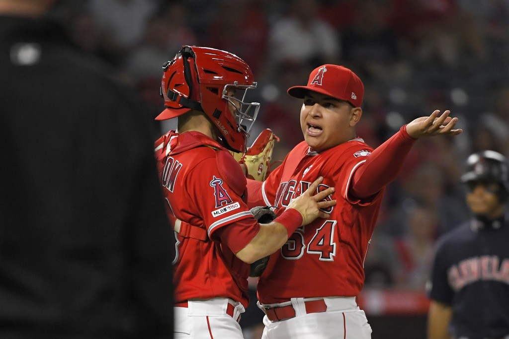 Los Angeles Angels' Jose Suarez, right, is held back by catcher Anthony Bemboom as he yells at Cleveland Indians' Yasiel Puig and manager Terry Franco...