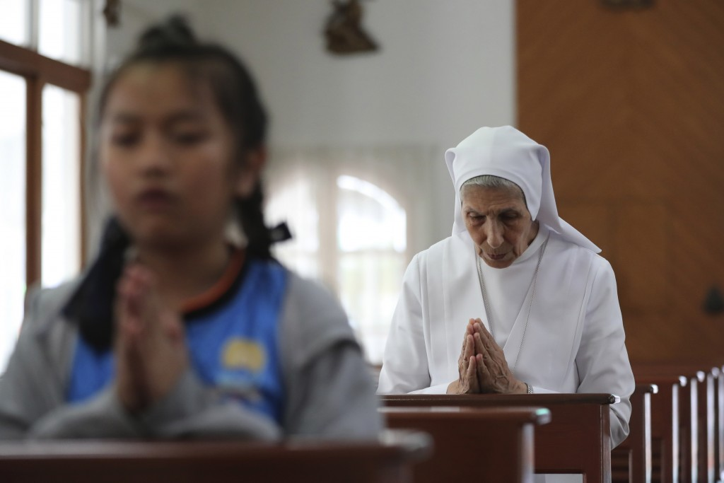 In this Aug. 27, 2019, photo, ST. Mary's School Vice Principal Sister Ana Rosa Sivori, right, prays with students inside a church at the girls' school