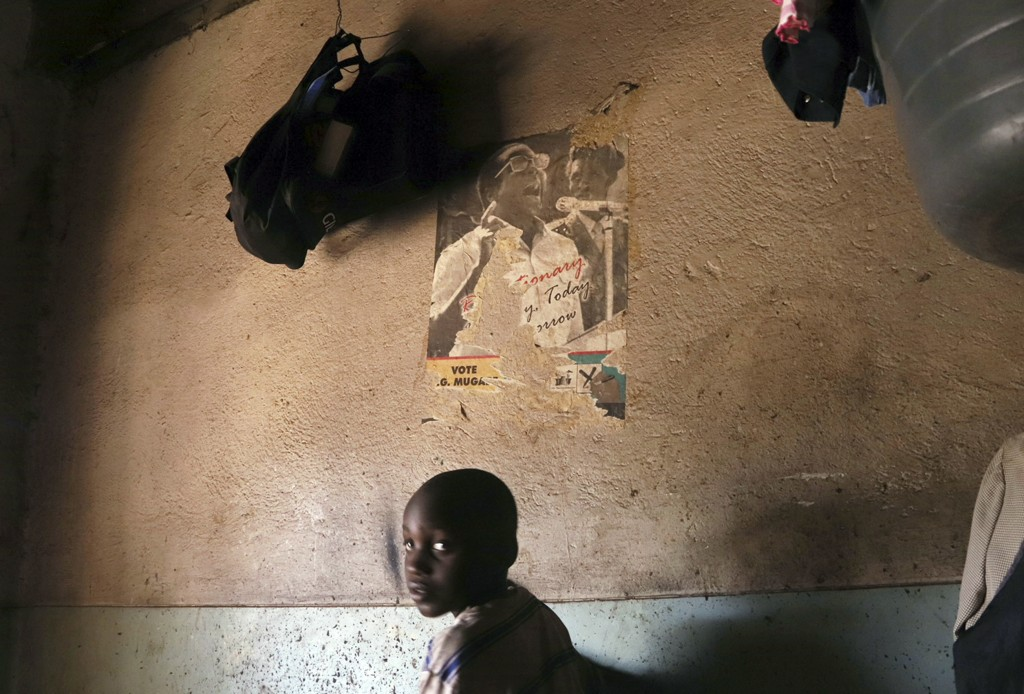A young child walks past a poster of former Zimbabwean President Robert Mugabe in a building in Harare, Sept. 6, 2019. Harare once enjoyed a reputatio...