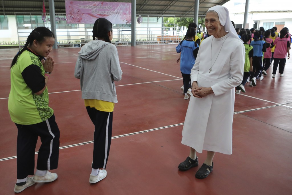 """In this Aug. 27, 2019, photo, Thai students give a Thai traditional greeting gesture of """"wai"""" to ST. Mary's School Vice Principal Sister Ana Rosa Sivo"""