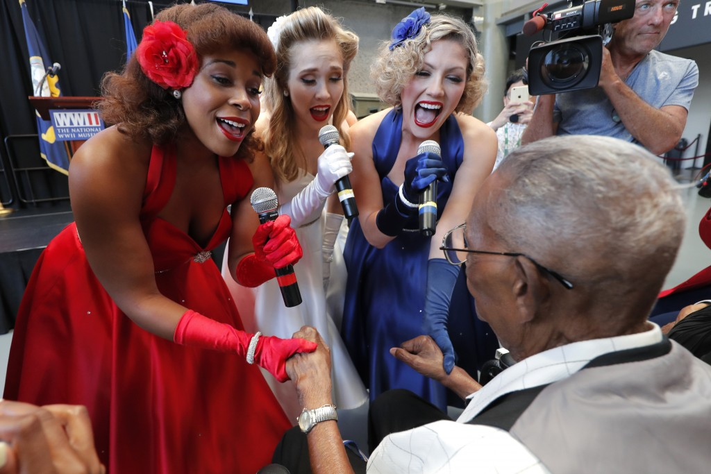 The Victory Belles hold the hands of World War II veteran Lawrence Brooks as they sing him happy birthday celebrating his 110th birthday at the Nation...