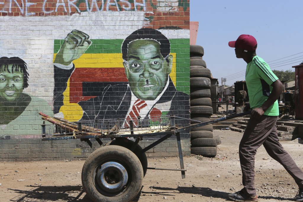 A man pushes an empty cart past a portrait of former Zimbabwean President Robert Mugabe in Harare, Sept. 6, 2019. Zimbabwe's capital, Harare, a city o