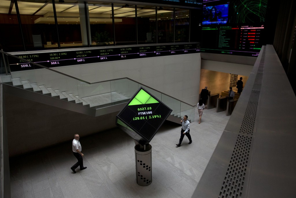 FILE - In this Tuesday, Aug. 25, 2015 file photo, Financial information is displayed on screens and a ticker inside the London Stock Exchange in the C
