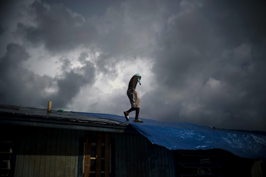 Trevon Laing walks the roof of his house to repair the damage made by Hurricane Dorian, in Gold Rock Creek, Grand Bahama, Bahamas, Thursday Sept. 12,