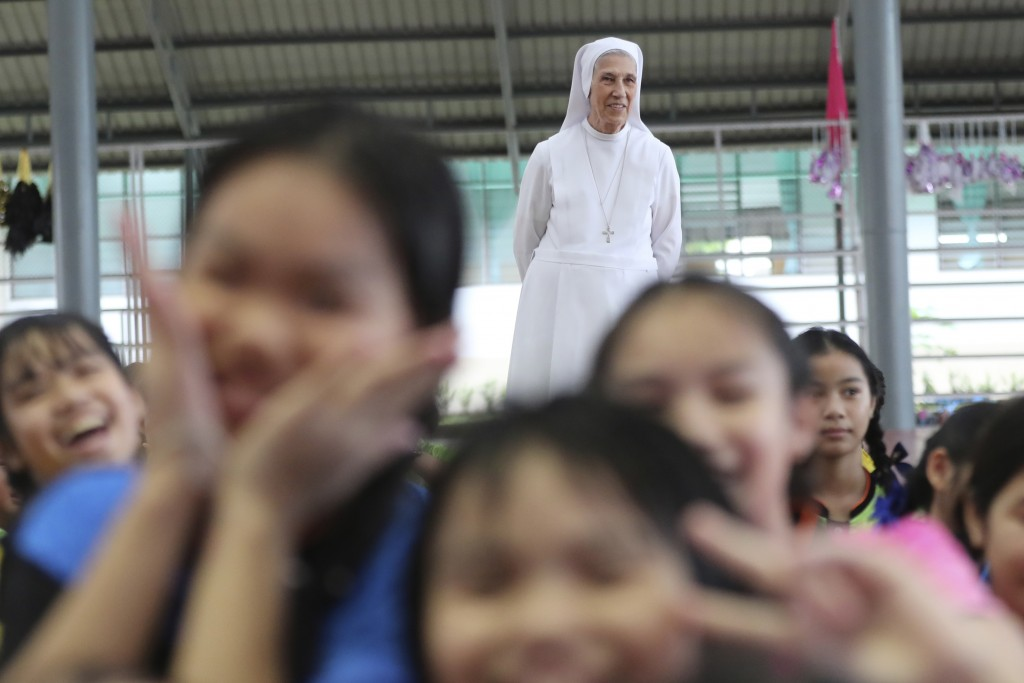 In this Aug. 27, 2019, photo, ST. Mary's School Vice Principal Sister Ana Rosa Sivori, rear, watches students play during a lunch break at the girls'