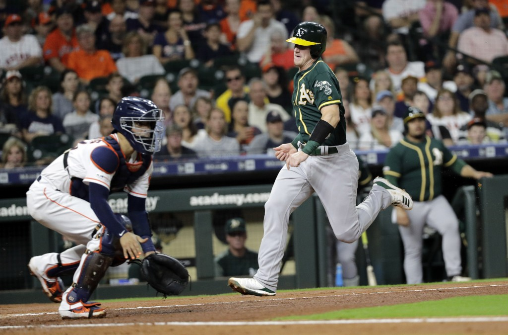 Oakland Athletics' Sean Murphy, right, scores as Houston Astros catcher Robinson Chirinos waits for the throw during the first inning of a baseball ga...