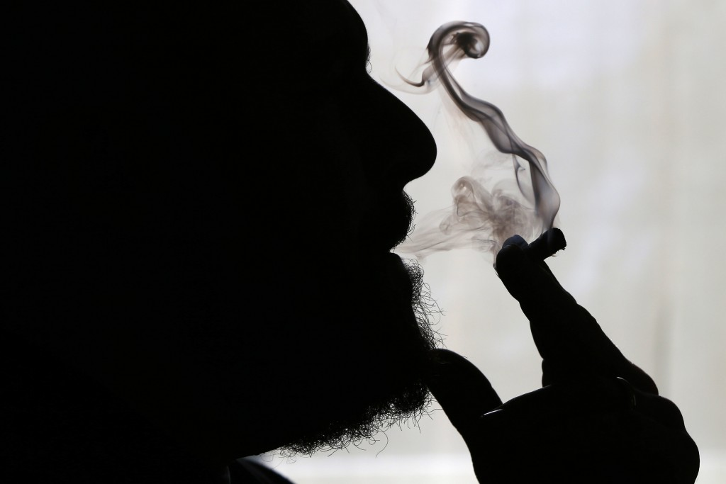 FILE - In this Nov. 21, 2014 file photo, a man smokes medical marijuana at his home in Belfast, Maine. Sniff and search is no longer the default for p...