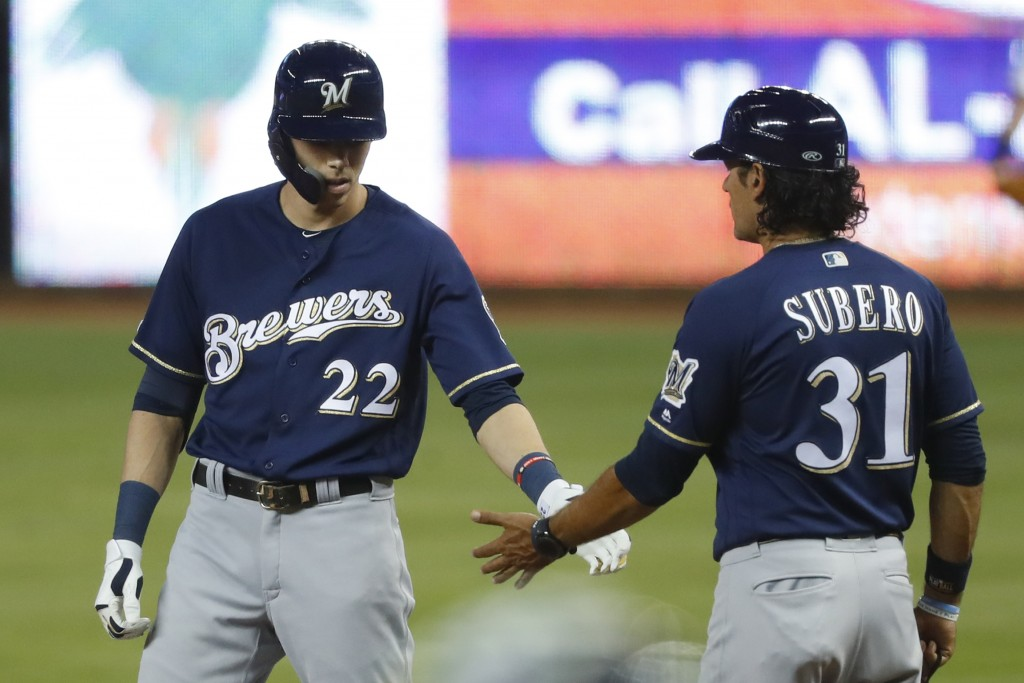 Milwaukee Brewers' Christian Yelich (22) is congratulated by first base coach Carlos Subero (31) after getting a base hit during the first inning of a...