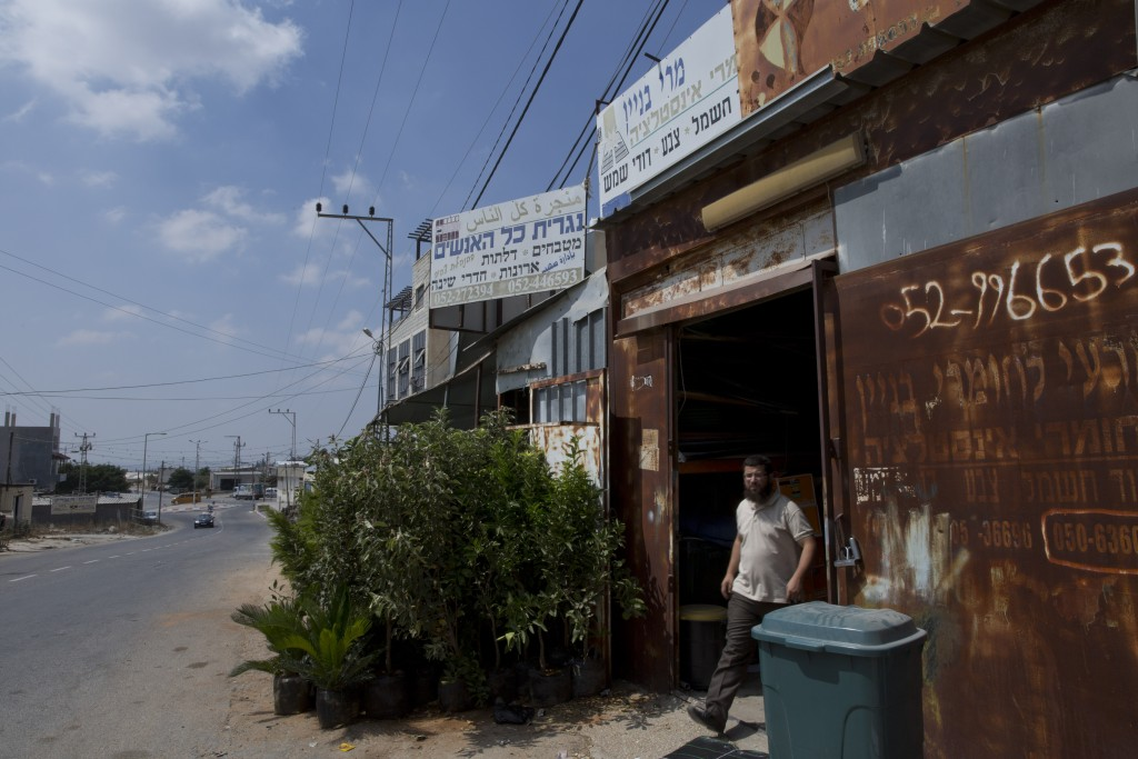 "In this Wednesday, Sept. 11, 2019 photo, a man walks out of a Palestinian carpentry shop under a sign in Arabic and Hebrew that reads, ""All the people..."