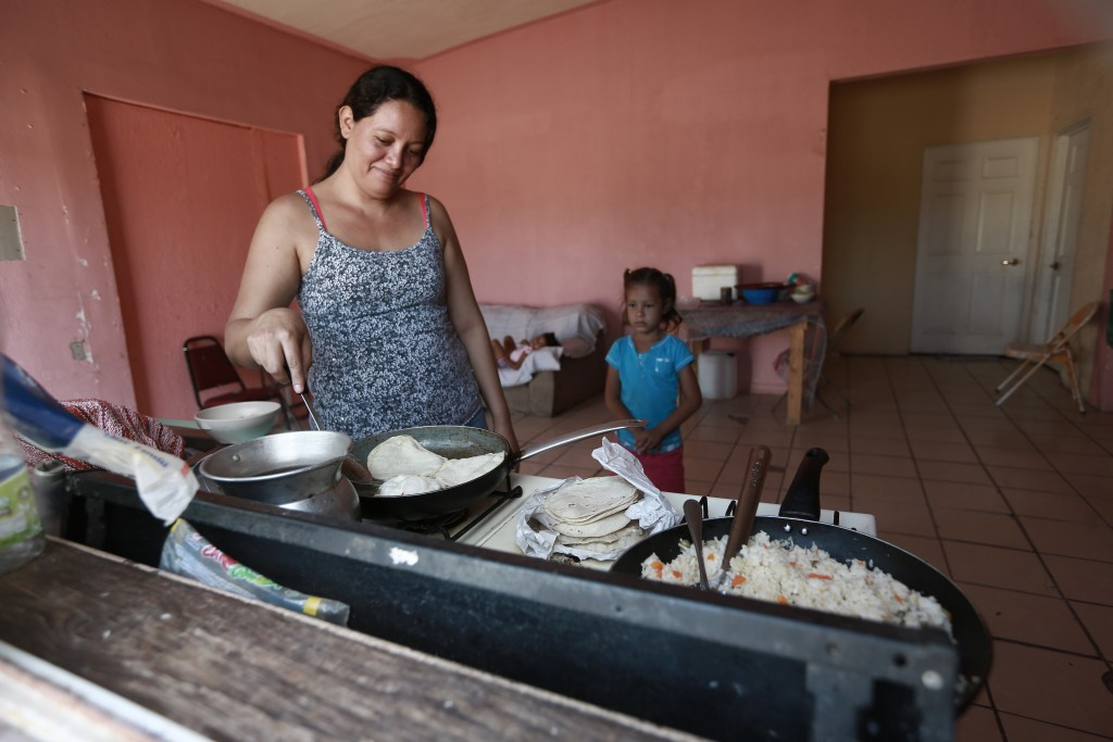 A Honduran migrant prepares tortillas and rice at the Pan de Vida shelter for migrants where she and her two daughters are living while waiting their